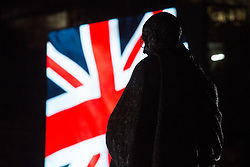 London, UK. 31 January, 2020. A statue of Gandhi in Parliament Square is silhouetted against a Union Jack appearing on a screen used for a Leave Means Leave rally on the evening on which the UK leaves the European Union.