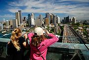 Two children view Sydney from atop the 87 metre high Sydney Harbour Bridge Pylon Lookout. Sydney, Australia