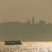 A passenger ferry passes across the Bosphorus Strait while the silhouette of the skyline of Sultanahment district can be seen through the haze in the distance.