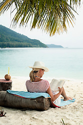 woman reading a book on the beach, Koh Lipe, Thailand