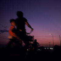 Asia, Laos, Vientiane, Blurred image of traffic on two-lane road just outside capital at dusk