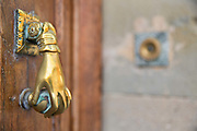Brass door knocker in the shape of a hand on old doorway, 10th May 2015, Esperaza, France.
