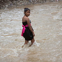 A young woman makes her way across water in El Calan after the bridge was washed away by hurricanes Eta and Iota.