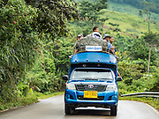 """26 OCTOBER 2016 - TAK, THAILAND:   A """"songthaew"""" or two seater bus on highway in Tak province. Songthaews are pickup trucks with two bench seats in the bed and used as local buses in rural Thailand.   PHOTO BY JACK KURTZ"""