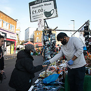 Ali selling face masks in Ridley Road Market 7th November 2020, East London, United Kingdom. Only a certain number of shoppers are allowed into the market, controlled by council workers because of the corona pandemic and lockdown. The UK Government introduced a 4 week lockdown from November 5th - December 2nd to combat the corona virus outbreak. It is the second national lockdown in the UK. It is the third day of the national lockdown and the lockdown restrictions mean that social restrictions are in place including social distance, people are only allowed to meet outside, in pairs and only if keeping social distance. Only if they already live together or have formed a social bubble can they interact freely.