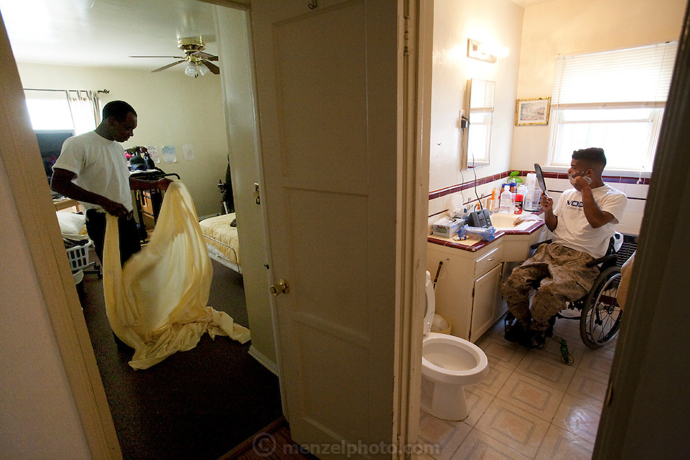 Felipe Adams, a 30-year-old Iraq war veteran who was paralyzed by a sniper's bullet in Baghdad, Iraq, shaves while his father changes his sheets at their home in Inglewood, California. (From the book What I Eat: Around the World in 80 Diets.) Felipe has already spent an hour in the bathroom going through his morning ritual.