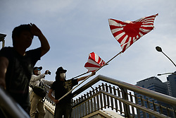 May 26, 2019 - Tokyo, Japan - A right-wing, nationalist protester holds an Imperial Japanese army flags towards demonstrators during a demonstration against the U.S president Donald Trump's forthcoming visit to Japan on May 26, 2019 in Tokyo, Japan. President Trump arrived on Saturday for a four-day state visit to Japan, the first official visit of the Reiwa era. (Credit Image: © Richard Atrero De Guzman/NurPhoto via ZUMA Press)