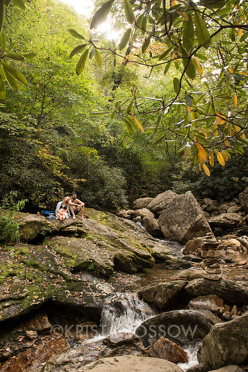 A couple enjoys the peace of nature at Skinny Dip Falls, a popular waterfall and swimming hole along the Blue Ridge Parkway in the Pisgah National Forest southwest of Asheville, North Carolina. The half-mile long trail is accessed from the parking lot at the Looking Glass Rock Overlook at milepost 417.