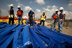 10 June 2010. Breton Sound Marina, Hopedale, Louisiana. USA.  <br /> Breton Sound Marina in Hopedale. Over 1,000 people now work in what was, just weeks ago empty fields. A city is rising out of the marshes to deal with the BP's catastrophic oil spill in the Gulf of Mexico. Workers load and unload, repair and haul miles and miles of oil boom. The 'hard boom' is not owned by BP or the federal government. It is leased with prices allegedly over $1.00 a linear foot per day. In St Bernard Parish alone there is over 200,000 linear feet of hard boom. Someone, somewhere is making a fortune on the back of this crisis. Workers are hired by contractors, who themselves are hired by bigger contractors. Yet again, the middle men are making a fortune on the backs of workers and on the back of this crisis. The scandal continues to grow.<br /> The ecological and economic impact of BP's oil spill is devastating to the region. Oil from the Deepwater Horizon catastrophe is evading booms laid out to stop it thanks in part to the dispersants which means the oil travels at every depth of the Gulf and washes ashore wherever the current carries it. The Louisiana wetlands produce over 30% of America's seafood and oil and gas production. They are the most fertile wetlands and nurseries of their kind in the world. BP's oil is killing everything.<br /> Photo; Charlie Varley/varleypix.com