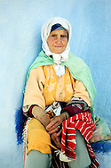 Morocco, Chefchaouen. Portrait of an elderly woman from Rif Mountains wearing a traditional dress.