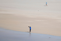 © Licensed to London News Pictures. 04/04/2020. Getty photographer travelled all the way from Plymouth in Devon during the lockdown.Surfing at Perranporth beach during the coronavirus lockdown. Cornwall UK. . Photo credit: Mark Hemsworth/LNP