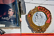 Perm, Russia, 01/06/2006..City bus driver dozing and listening to music with a huge Order Of Lenin symbol, erected in 1971, behind.