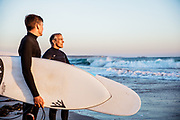 Father and son holding their surfboards at the waters edge at St Ouen's Bay, Jersey, ready to go in for a surf at sunset.
