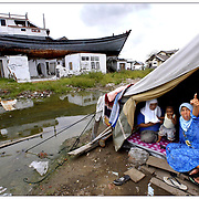An Indonesian woman recounts her terrifying story of survival after the 2004 tsunami destroyed her home and took the lives of her children and husband in Banda Aceh, Indonesia. The storm swept across the Indian Ocean, killing more than 230,000 people and leaving millions homeless throughout Asia. The boat sitting on a neighbour's home became a refuge for dozens of people that clung to it to avoid being swept out to sea when the ocean receded