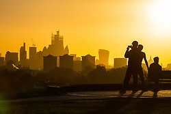 People enjoy the spectacular sunrise as day breaks over London's skyline, seen from Primrose Hill, to the north of the city. London, November 13 2018.