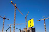 Germany, Cologne, cranes on the the construction site of the building project MesseCity Koeln near the exhibition center in the district Deutz, signpost for pedestrians.<br /> <br /> Deutschland, Koeln, Kraene auf der Baustelle des Grossprojektes MesseCity Koeln neben dem Messegelaende, Wegweiser fuer Fussgaenger.