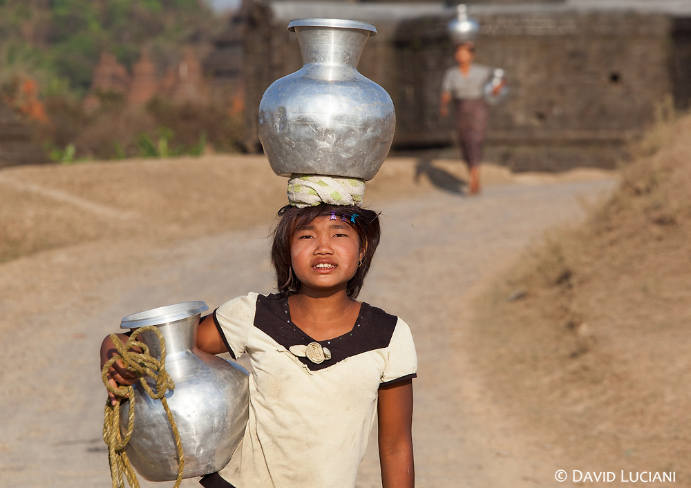 A girl with two aluminium water pots. These pots are usually imported from Bangladesh.