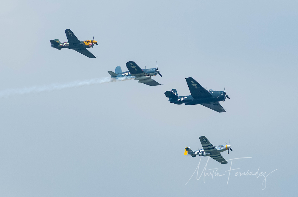 From left to right, a Curtiss P-40 Warhawk, a Vought F4U Corsair, a Grumman TBM Avenger, and a North American P-51 Mustang, perform the Missing Man formation during the Arsenal of Democracy flyover.