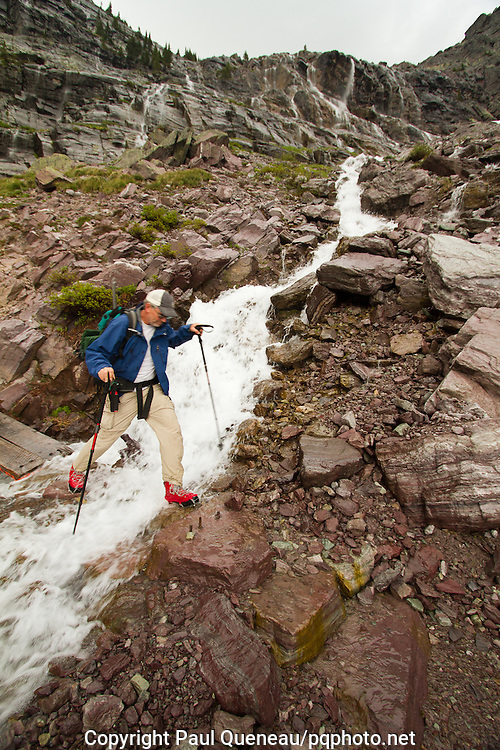 A backpacker steps across Feather Woman Falls as it cascades down Glacier Basin in Montana's Glacier National Park near Sperry Chalet en route to Sprague Creek and Lake McDonald.