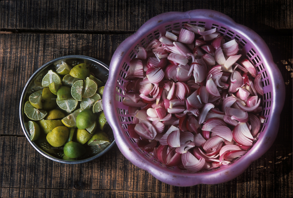 Red onion and slices of lime, the Indian equivalent of salt and pepper, on a table at a road side dhaba (restaurant) in Ahmedabad, Gujarat.