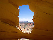 """Sandstone Window near Melody Arch, in the vicinity of North Coyote Buttes area known as """"The Wave,"""" Vermillion Cliffs National Monument, Arizona, known for its beautiful rock formations. The area known as White Pocket is in the distance."""