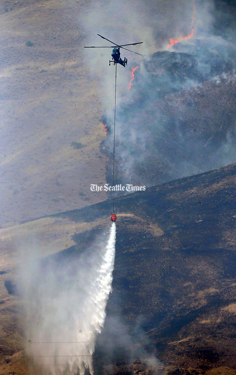Helicopters dump water from the Columbia River onto the Mills Canyon wildfire Thursday. (Photo by Bettina Hansen / The Seattle Times, 2014)