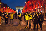 December, 8th, 2018 - Paris, Ile-de-France, France: Protesters on Champs Elysees with Christmas lighting at night. The French 'Gilets Jaunes' demonstrate a fourth day. Their movement was born against French President Macron's high fuel increases. They have been joined en mass by students and trade unionists unhappy with Macron's policies. Nigel Dickinson