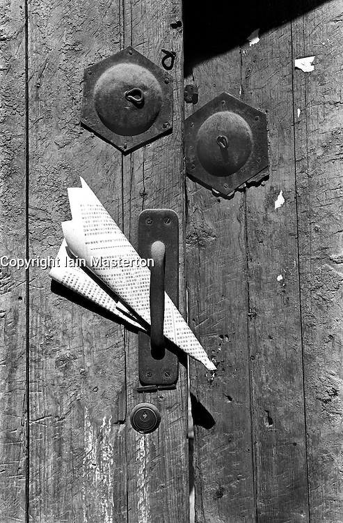 Newspaper stuck in handle of an old door to traditional house in a Beijing hutong