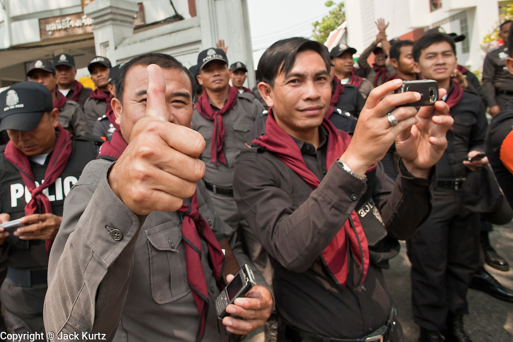 """Mar. 27, 2010 - BANGKOK, THAILAND:  Thai police officers, who are supposed to control the Red Shirts protests, applaud, photograph and cheer for the Red Shirts as they march through Bangkok Saturday, March 27. More than 80,000 members of the United Front of Democracy Against Dictatorship (UDD), also known as the """"Red Shirts"""" and their supporters marched through central Bangkok March 27 during a series of protests against and demand the resignation of current Thai Prime Minister Abhisit Vejjajiva and his government. The protest is a continuation of protests the Red Shirts have been holding across Thailand. They support former Prime Minister Thaksin Shinawatra, who was deposed in a coup in 2006 and went into exile rather than go to prison after being convicted on corruption charges. Thaksin is still enormously popular in rural Thailand.    PHOTO BY JACK KURTZ"""