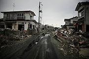 Les abords de la route principale sont les premières zones où les rues et les maisons ont été nettoyées. Mais lorsquon sécarte pour pénétrer les anciens quartiers résidentiels, on saperçoit quil reste beaucoup à faire. Il ny a pas de répit pour lil, absolument tout est marqué par la vague. Les perspectives sont accentuées par le vide laissé au-dessus des fondations. Les volumes architecturaux ont perdu leur rigidité et beaucoup devront être détruits.