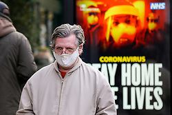 "© Licensed to London News Pictures. 09/01/2021. London, UK. A man wearing a protective face covering walks past the Government's ''Stay Home, Save Lives' Covid-19 publicity campaign poster in north London, as the number of cases of the mutated variant of the SARS-Cov-2 virus continues to spread around the country. Prime Minister Boris Johnson has said that the public should ""stay at home"". Photo credit: Dinendra Haria/LNP"