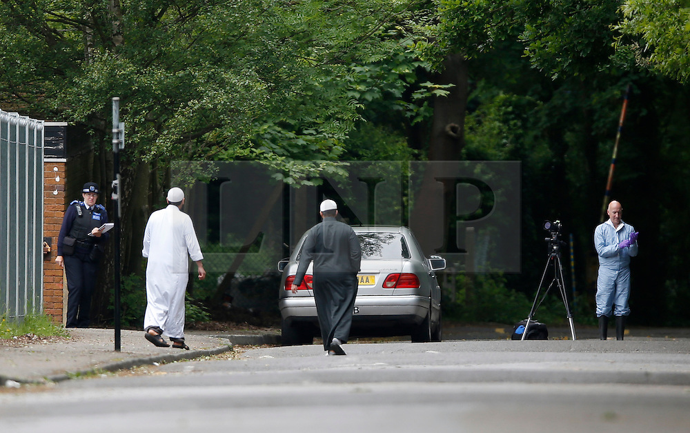 © Licensed to London News Pictures. 09/06/2013, London, UK.  A police officer, left, stands guard at the gate while a forensic officer, right works outside the  Darululoom Islamic boarding school in Chislehurst, southeast London where a 'suspicious' fire broke out, Sunday, June 9, 2013. Photo credit : Sang Tan/LNP