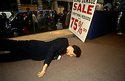 A menswear shop mannequin lies on the ground of the store at Liverpool Street, days after a terrorist bomb in nearbny Bishopsgate. Crowds of bargain hunters queue outside to buy damaged stock after the blast. Everything is reduced by up to 75% off this shop and others like it are popular as Londoners make the best of troubled times again. The Irish Republican Army (IRA) exploded a truck bomb on Bishopsgate. Buildings up to 500 metres away were damaged with one and a half million square feet (140,000 m) of office space being affected and over 500 tonnes of glass broken. Repair costs reached approx £350 million. It was said that Roman remains could be viewed at the bottom of the pit the bomb created. One person was killed when the one ton fertiliser bomb detonated directly outside the medieval St Ethelburga's church.