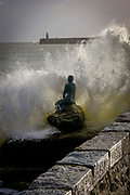 A large wave crashes over Cornelia Parker's Mermaid statue on Sunny Sands Beach on 8th December 2018 in Folkestone, Kent, United Kingdom. The Folkestone Harbour Arm and lighthouse can be seen in the horizon.