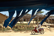 A man rides a scooter down a street in the village of Popoko, Bas-Sassandra region, Cote d'Ivoire on Tuesday March 6, 2012.