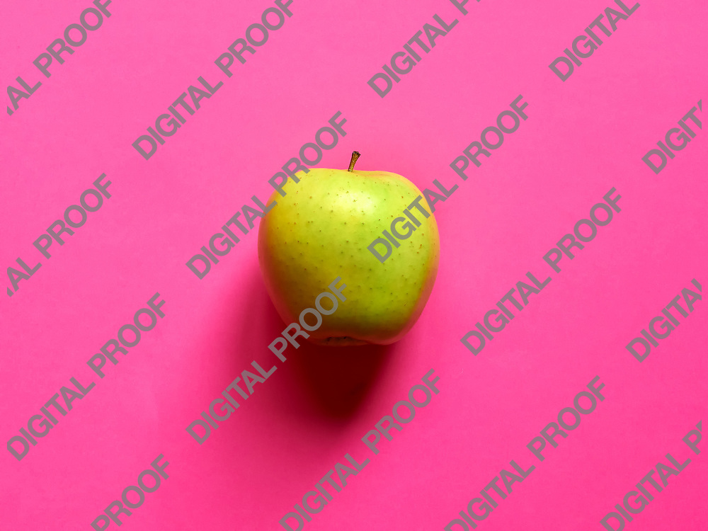 Above view of a Green apple isolated in a fuschia background in studio