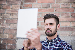 Young man taking selfie with digital tablet against brick wall, Munich, Bavaria, Germany