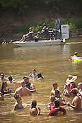 A airboat drives through people wading in the Oconee River during the annual Summer Redneck Games Dublin, GA.