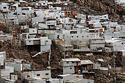 Houses are built with zinc sheets beside the mountains where a gold mine is located. City of Rinconada is located at 5400 meters above sea level in the Peruvian Andes. People have set up a system of hoses to take water from the glacier at top of the mountain.