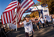 Carrying two 6-foot tall American flags high, Korean War Army veteran Bob Kohler, 85, of Irvine, CA, crosses the finish line of the Dana Point Turkey Trot masters 5K in Dana Point, CA. Pinned to his chest are the photos of two service members who were killed in combat in Iraq.