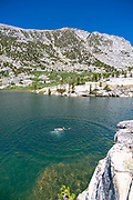 A teenage boy swims at Sallie Keyes Lakes along the John Muir Trail; John Muir Wilderness, Sierra National Forest, Sierra Nevada Mountains, California, USA.