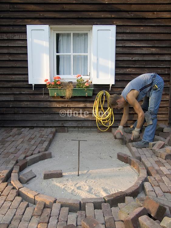 cobblestone bricklayer making an ornamental pavement