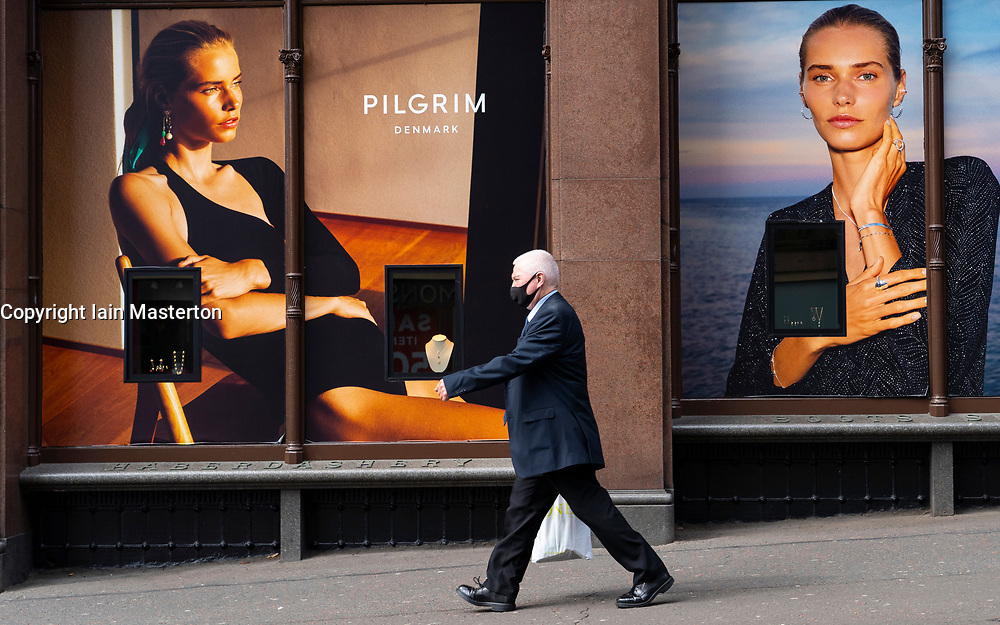 Edinburgh, Scotland, UK. 28 July, 2020. Business and tourism slowly returning to the shops and streets of Edinburgh city centre. A man walks past shop window advertising display in Jenners department store. The retail industry is suffering severe problems with many job losses. Iain Masterton/Alamy Live News