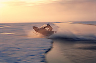 Skidooing on June sea ice in midnight light, Pond Inlet, Canada