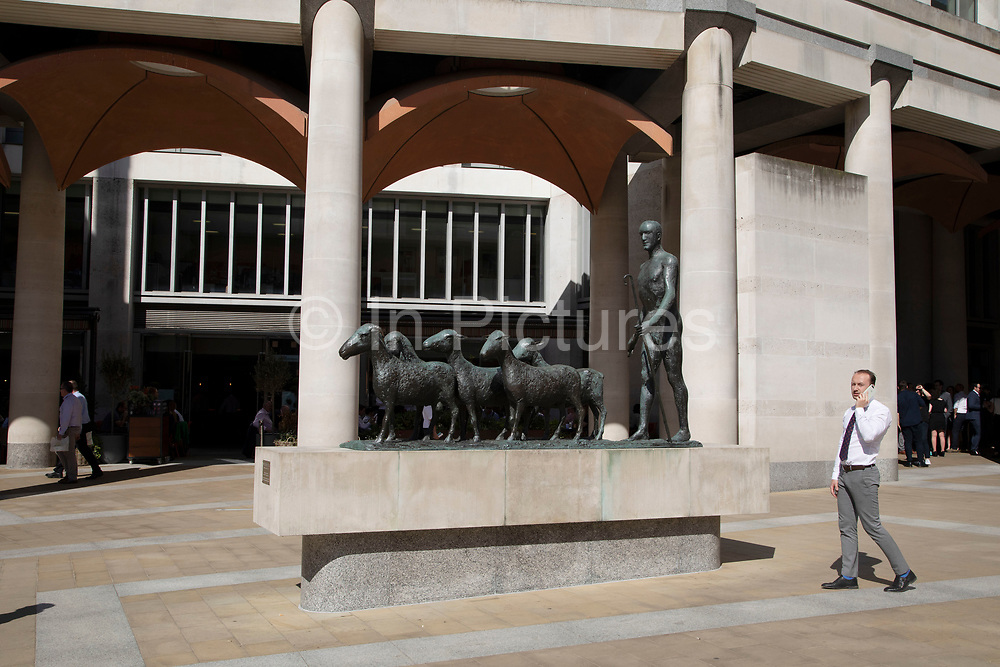 Architecture of Paternoster Square is softened by a sculpture of a figure hearding sheep as they once did through the City of London, England, United Kingdom.
