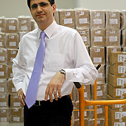 Portrait of VivaCell- Armenia CEO Ralph Yirikian in front of packed SIM cards at his office headquarters in Yerevan, the capital of Armenia.