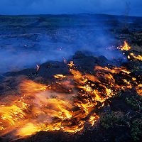 USA, Hawaii, Volcanoes National Park,  Wildfires burn as molten lava pours across grass-covered old lava below Kilauea volcano
