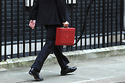 © Licensed to London News Pictures. 21/03/2012. Westminster, UK. British Chancellor of the Exchequer George Osborne holds his red ministerial box as he poses for pictures outside 11 Downing Street in London, on March 21, 2012. The Chancellor is expected to raise the amount of money people can earn before income tax takes hold and impose a new levy on the purchase of expensive homes. Photo credit : Stephen SImpson/LNP