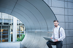 Businessman leaning against modern architecture and working on laptop, Munich, Bavaria, Germany