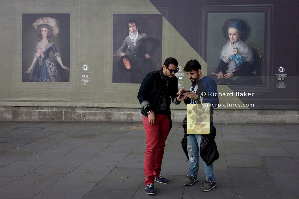 Tourists look at their handheld device near Goya portraits, sponsored by Credit Suisse and advertised on a construction hoarding outside the National Portrait Gallery.